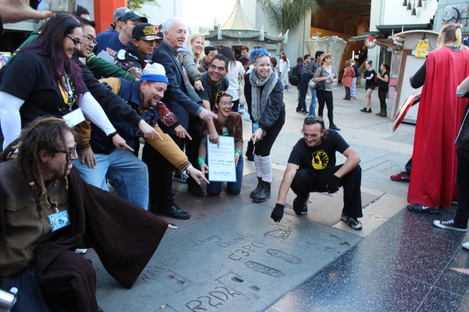 Taking a photo of the Star Wars footprints with Anthony Daniels